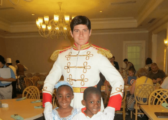 Disney prince charming in character with two children
