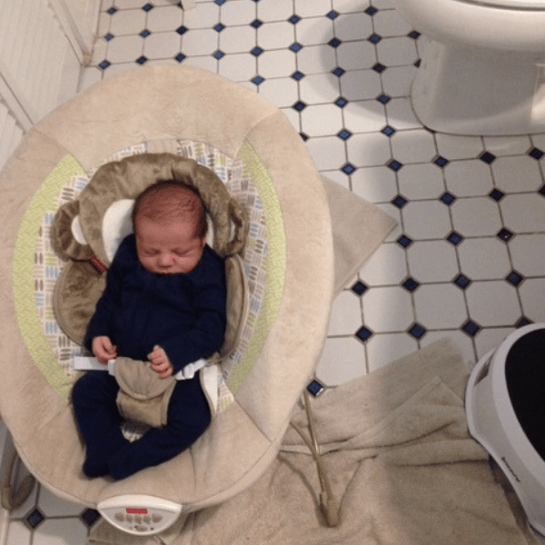 newborn baby sleeping in bouncer on bathroom floor